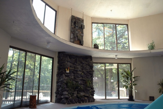 The 2-story pool tower with its stone wall and art installation