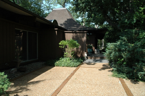 The aggregate walkways with cedar beam dividers are both mid-century appropriate and timeless