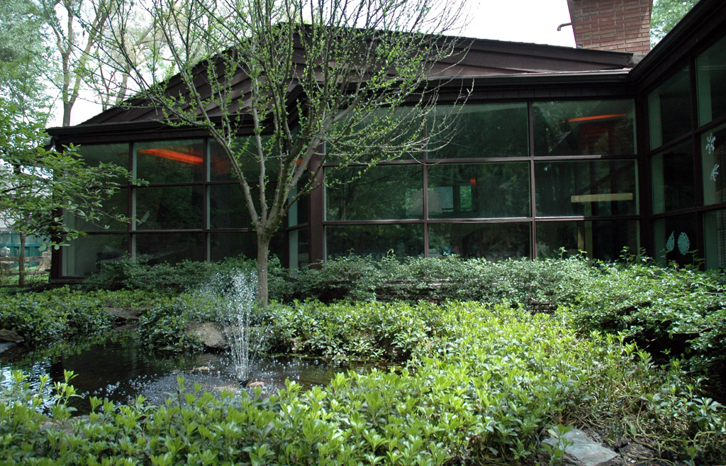 Looking into the living room / dining room from over the landscaping and fountain in the back