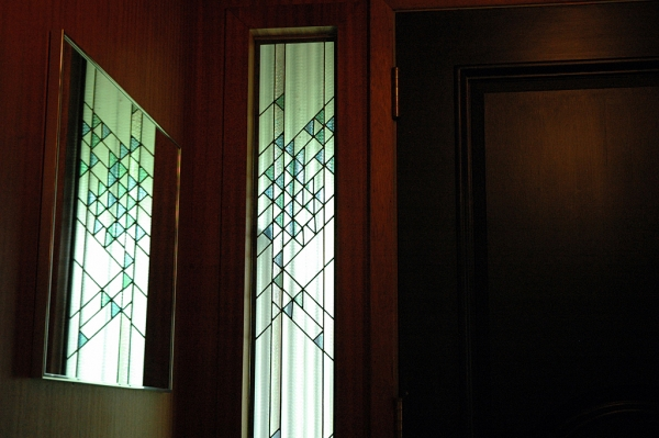 The stained glass window Rick designed for the sidelight is very strong thanks to the diagonal lines. Through the sidelight you can still make out the home's original wavy green glass.