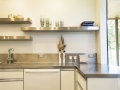 The Kitchen worktop is a seamless stainless steel surface with integrated sink, custom-fit by Elkay. Open shelves keep the space airy and bright