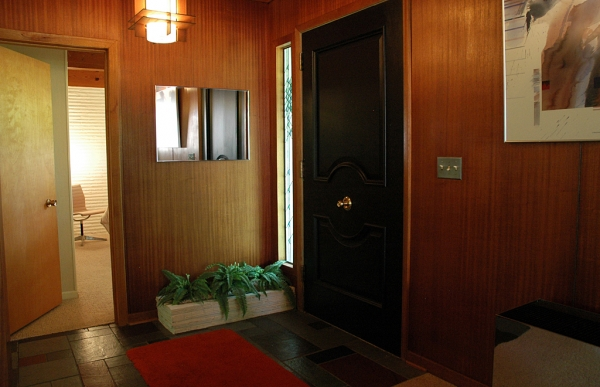 The smaller planter outside the front door is carried into the entryway. Note the center knob on the door. Wall panels are mahogany.