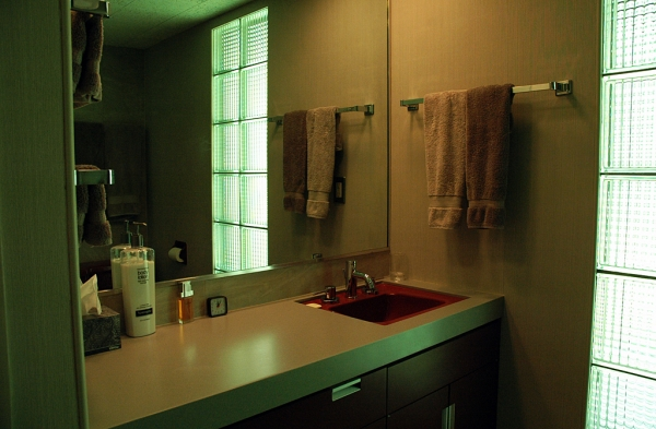 The remodeled bathroom was originally the only one in the house. The original sink and toilet remain, now with a countertop made to look like concrete, and cabinetry that matches the style of the kitchen cabinets.