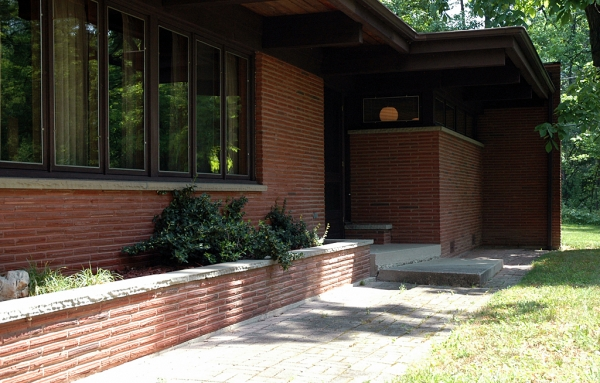 Walking up to the front door, you see two integrated planters. The one by the front door carries through to the inside.